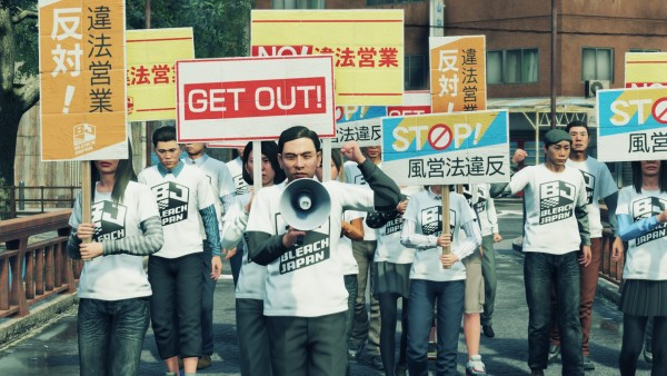 "Yakuza: Like a Dragon. Bleach Japan marches with conservative signs, mostly in Japanese - the words ""NO!,"" ""GET OUT!,"" AND ""STOP!"" are written in English."